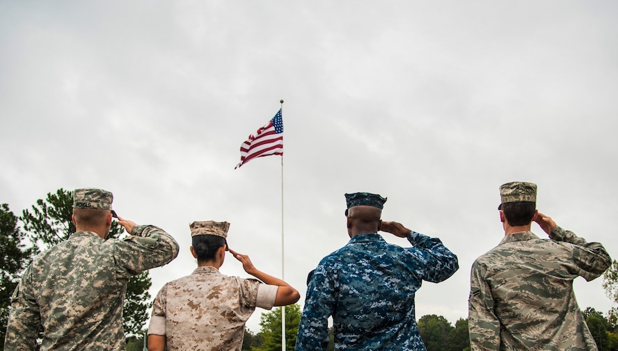 Service members salute the American flag during a retreat ceremony Oct. 2, 2014, at Little Rock Air Force Base, Ark. The four military members represented each branch of the U.S. military and assembled to show solidarity. (U.S. Air Force photo/Airman 1st Class Harry Brexel)