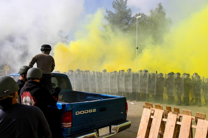 Arizona National Guard, 1st Battalion, 158th Infantry Regiment Soldiers, together with Moldovan soldiers, face an aggressive crowd of rioters throwing smoke and rocks during a situational training exercise as part of Steppe Eagle 2014 exercise, Oct. 4, at the Joint Multinational Readiness Training Center in Hohenfels, Germany.