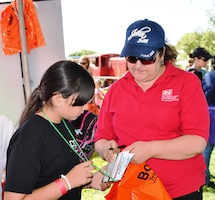BERNALILLO, N.M., -- Jeannette Alderete assists a Girl Scout at the Corps' STEM Camporee booth, Sept. 13, 2014.