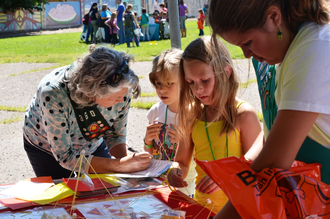 BERNALILLO, N.M., -- Carol Wies-Brewer assists some Scouts as they design and build a structure with spaghetti and marshmallows.