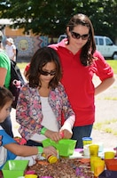 BERNALILLO, N.M., -- Amanda Tapia-Pittman watches as Girl Scouts design and build dams with gravel and playdough.