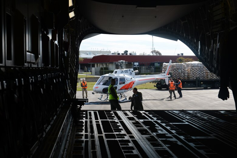 An Eurocopter AS350 B2 single engine helicopter without its blades attached, along with pallets of cargo, are staged behind a Joint Base Lewis-McChord C-17 Globemaster III prior to being loaded Oct. 8th, 2014, at Christchurch, New Zealand. The helicopter was transported along with the cargo and 62 passengers to McMurdo Station in support of Operation Deep Freeze. (U.S. Air Force photo/Master Sgt. Todd Wivell)