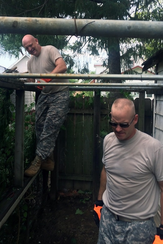 Lt. Col. Michael Sexton seeks to balance himself on a fence he intends to repair during a recent volunteer mission with the Omaha District.
