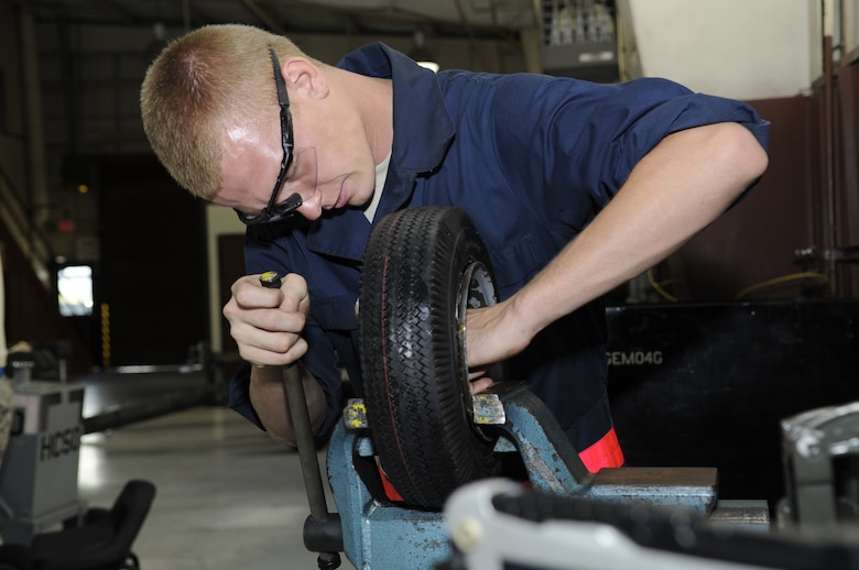 U.S. Air Force Airman 1st Class Jonathan Baker, 355th Equipment Maintenance Squadron aerospace ground equipment journeyman, uses a bench vise to lock a wheel in place in order to replace its inner tube at Davis-Monthan Air Force Base, Ariz., Oct. 9, 2014. Replacing the tube can be difficult because if it is not installed correctly, it can get pinched in between the steel rim and the tire, causing the tube to explode when inflated. (U.S. Air Force photo by Airman 1st Class Betty R. Chevalier/Released)