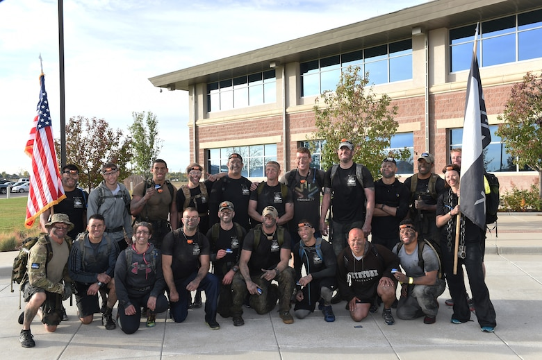 Team Buckley members pose for a final picture after a five-hour long ruck march through water drains and swimming through Lake Williams with 25-pound rucksacks on their backs Oct. 8, 2014 during the Team Cohesion Challenge on Buckley Air Force Base, Colo. The challenge, hosted by GORUCK, began long before sunrise and incorporated grueling special operations-type training activities. (U.S. Air Force photo by Airman 1st Class Samantha Saulsbury/Released)