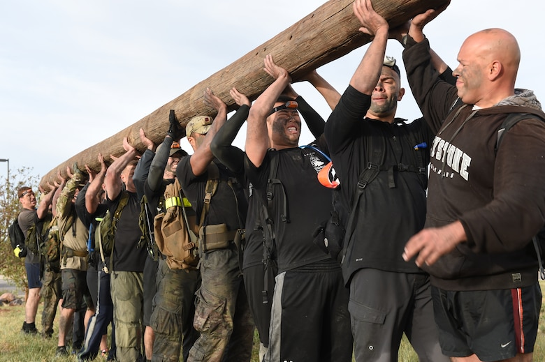 Buckley's Team Cohesion Challenge team lifts a wooden telephone pole above their heads Oct. 8, 2014, during the Team Cohesion Challenge on Buckley Air Force Base, Colo. The five-hour long challenge, hosted by GORUCK, began long before sunrise and consisted of crawling through water drains and swimming through Lake Williams with 25-pound rucksacks on their backs. (U.S. Air Force photo by Airman 1st Class Samantha Saulsbury/Released)
