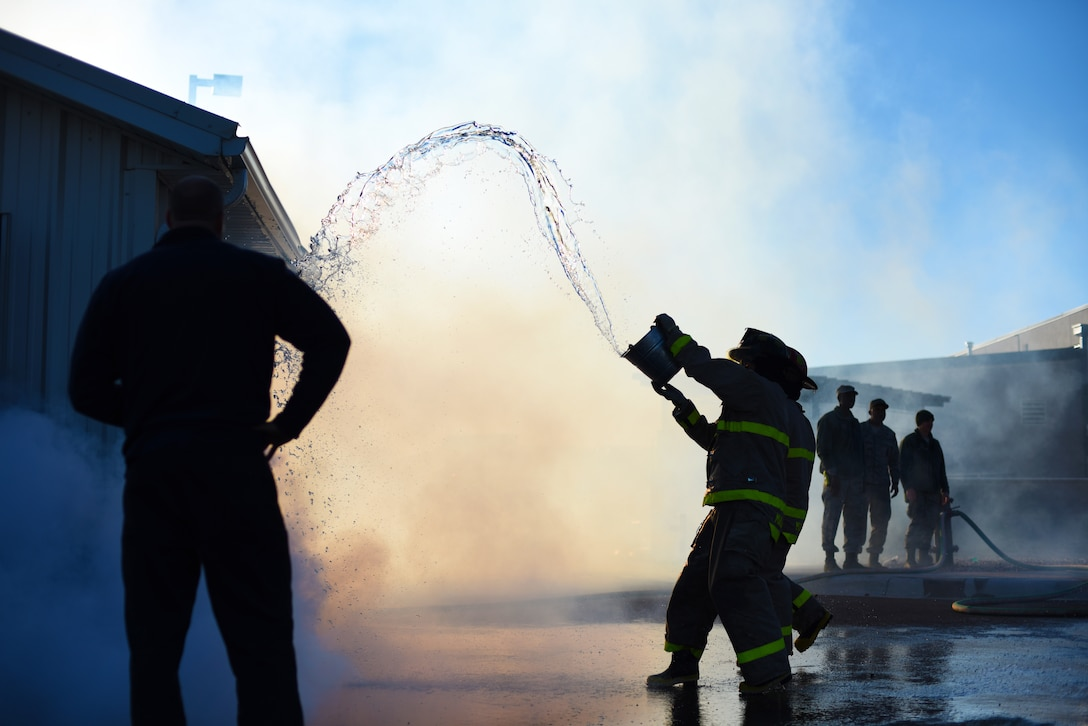 An Airman throws water onto a simulated burning building during Malmstrom Air Force Base's fourth annual Fire Prevention Week fire muster Oct. 10. While completing this station, contestants were required to fill a 55-gallon drum by throwing water onto the roof of the structure and having the runoff drain into the barrel. (U.S. Air Force photo/Airman 1st Class Collin Schmidt)