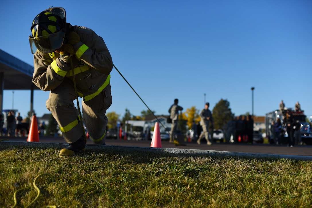 An Airman with the 341st Civil Engineer Squadron pulls a weighted sled during Malmstrom Air Force Base's fourth annual Fire Prevention Week fire muster Oct. 10. The challenge consisted of about 10 different stations where competitors had to work as a team and muster all their strength to finish with the best time. (U.S. Air Force photo/Airman 1st Class Collin Schmidt)