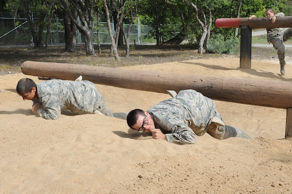 Basic military trainees craw under and over logs as a part of the basic military training obstacle course at Joint Base San Antonio-Lackland, Sept. 24, 2014. The obstacle course was about a mile to a mile and a half long depending on what 14 obstacles were open; the two water obstacles would close seasonally. The course, which closed Sept. 24, was replaced by new one, called the Leadership Reaction Course, which was added to basic expeditionary Airmen's training, also known as BEAST week, at JBSA-Lackland Medina Annex and became fully operational Sept. 29. (U.S. Air Force photo by Senior Airman Krystal Jeffers/Released)