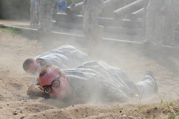 Basic military trainees low craw through sand as part of the basic military training obstacle course Sept. 24, 2014 at Joint Base San Antonio-Lackland. The mile-and-a-half long course, which permanently closed the same day, was replaced with the 'Leadership Reaction Course' at JBSA-Lackland Medina Annex, which became fully operational Sept. 29. The new course was integrated into the Creating Leaders, Airmen, and Warriors – or CLAW – mission which is part of the basic expeditionary Airmen's training, also known as BEAST week. (U.S. Air Force photo by Senior Airman Krystal Jeffers/Released)