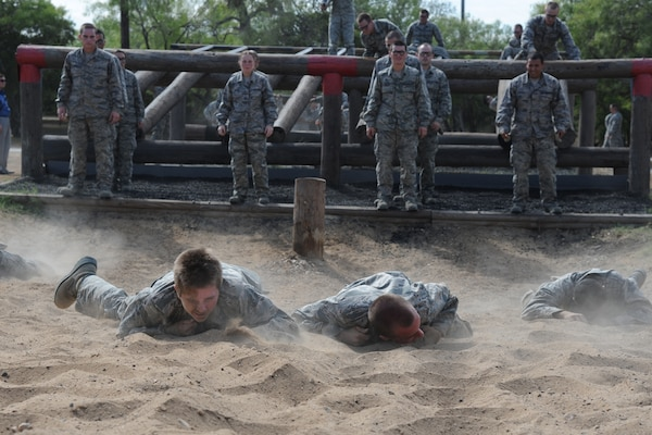 Basic military trainees low craw through sand as part of the basic military training obstacle course at Sept. 24, 2014, Joint Base San Antonio-Lackland. The mile-and-a-half long course, which permanently closed the same day, was replaced with the 'Leadership Reaction Course' at JBSA-Lackland Medina Annex, which became fully operational Sept. 29. The new course was integrated into the Creating Leaders, Airmen, and Warriors – or CLAW – mission which is part of the basic expeditionary Airmen's training, also known as BEAST week. (U.S. Air Force photo by Senior Airman Krystal Jeffers/Released)