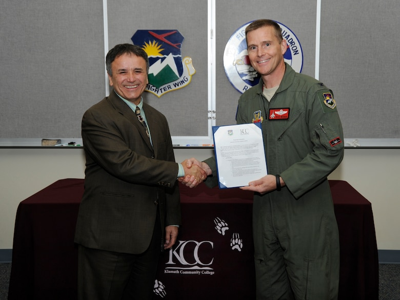 Oregon Air National Guard Col. Richard W. Wedan, 142nd Fighter Wing Commander, right, and Dr. Roberto Gutierrez, President of Klamath Community College, left, pause for photograph during the signing ceremony of a Memorandum of Understanding between the college and the 142nd Fighter Wing, Oct. 7, Portland Air National Guard Base, Ore. (U.S. Air National Guard photo by Tech. Sgt. John Hughel, 142nd Fighter Wing Public Affairs/Released)