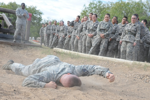 Staff Sgt. Dennis Weis, 323rd Training Squadron military training instructor, demonstrates how to complete one of the obstacles for trainees at the basic military training obstacle course, which included performing the low crawl, Sept. 24, 2014 at Joint Base San Antonio-Lackland,. The trainees completed the last run of course before its permanent closure the same day. A new course, called the Leadership Reaction Course, was added to basic expeditionary Airmen's training, also known as BEAST week, at JBSA-Lackland Medina Annex and became fully operational Sept. 29. (U.S. Air Force photo by Senior Airman Krystal Jeffers/Released)