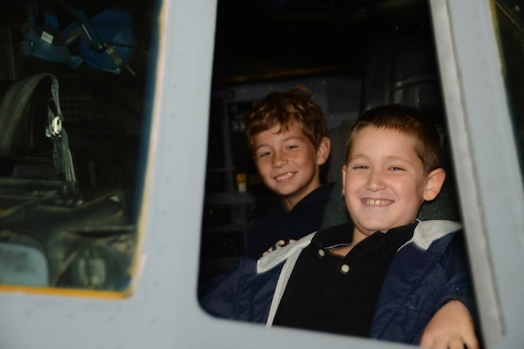 Nathan Defreitas, 8, sits in the cockpit of a C-130H Hercules aircraft with Colton Fillmore, 8, looking on behind him at Bradley Air National Guard Base, East Granby, Conn., Oct. 4, 2014. Defreitas and Fillmore both  participated in a base tour given to employees of Fillmore Express Inc. (Air National Guard photo by Senior Airman Jennifer Pierce)