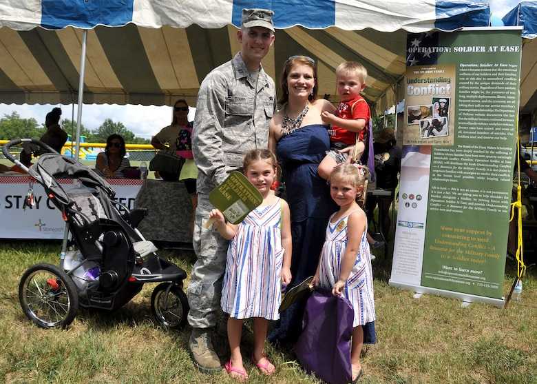 Capt Jeremy Dobbs, 80th Aerial Port Squadron, navigates through Family Day  with his wife Kimberly, two daughters Callie and Eva and his son Elijah Sept. 6, 2014, at Dobbins Air Reserve Base, Ga. The annual event is an opportunity for reserve members and their families to get together for some fun and camaraderie. (U.S. Air Force photo by Staff Sgt. Karla V. Lehman/Released).