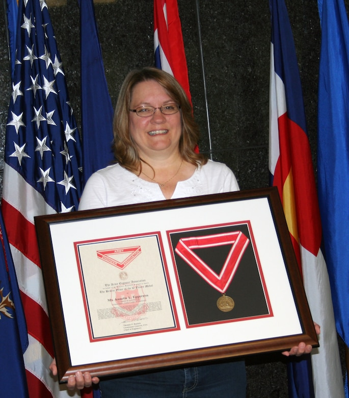 Annette Epperson holds up her Bronze de Fleury medal she received for her more  than 37 years of dedicated service to the United States Army Corps of  Engineers.