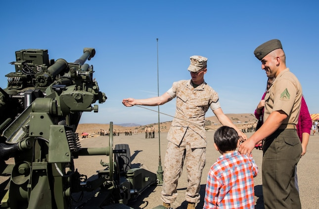 U.S. Marine Cpl. Jonathan Lira, right, shows his son an M777A2 Lightweight Howitzer used by Marines after the composite ceremony for the 15th Marine Expeditionary Unit aboard Camp Pendleton, Calif., Oct. 10, 2014. Lira, 26, from El Paso, Texas, is an administrative specialist with the 15th Marine Expeditionary Unit. (U.S. Marine Corps photo by Sgt. Emmanuel Ramos/Released)
