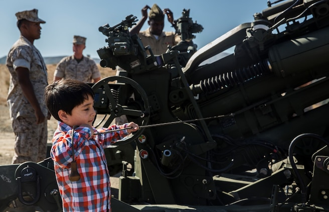 A U.S. Marine's son pulls the lanyard on an M777A2 Lightweight Howitzer after the composite ceremony for the 15th Marine Expeditionary Unit aboard Camp Pendleton, Calif., Oct. 10, 2014. (U.S. Marine Corps photo by Sgt. Emmanuel Ramos/Released)