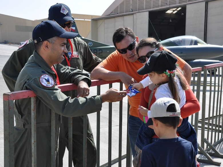 Lt. Col. Raul Rosales, detachment commander from the Texas Air National Guard's 149th Fighter Wing at Joint Base San Antonio, Texas, hands a unit patch to a Chilean child during an Open Day at Exercise Salitre 2014 Oct. 11 at Cerro Moreno Air Base, Chile. More than 80 Airmen from the Texas and Ohio Air National Guard are taking part of the Chile-led exercise which also features air forces from Brazil, Argentina and Uruguay. (U.S. Air Force photo by Capt. Bryan Bouchard/Released)