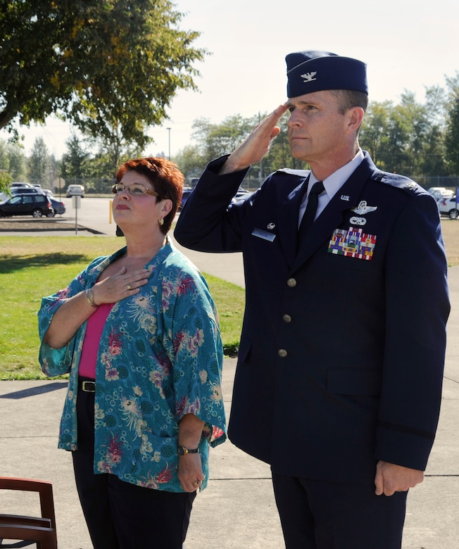 Col. Rick Wedan, 142nd Fighter Wing Commander and Ms. Mary Bell render proper respect to the American Flag during the singing of the national anthem during a retirement ceremony held for Bell at the main flag pole of the Portland Air National Guard Base, Ore., Oct. 4, 2014. (U.S. Air National Guard photo by Tech. Sgt. John Hughel, 142nd Fighter Wing Public Affairs/Released)