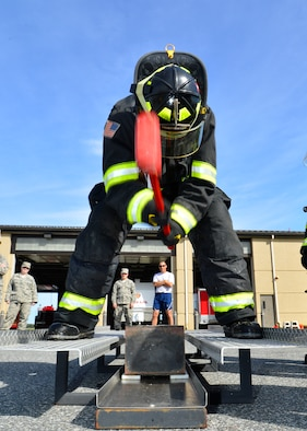 A competitor hits a Kaiser sled during the 2014 436th Civil Engineer Squadron Fire Department Muster Oct. 9, 2014, at Dover Air Force Base, Del. The force needed to move the sled simulates the force needed for firefighters to gain forcible entry into a structure. (U.S. Air Force photo/Airman 1st Class William Johnson)