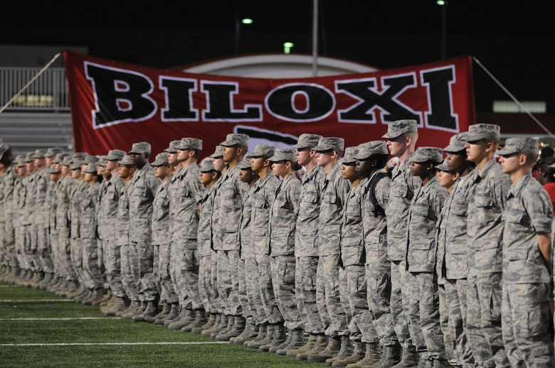 Airmen from Keesler Air Force Base stand along the sideline of the Biloxi football stadium during the preliminary festivities for the Biloxi High School Military Appreciation Night football game against Ocean Springs High School Oct. 10, 2014.  Keesler leadership also participated in the preliminary events by conducting the official coin toss and meeting with the head coaches, referee staff and team captains.  Ocean Springs defeated Biloxi 35-21.  (U.S. Air Force photo by Kemberly Groue)