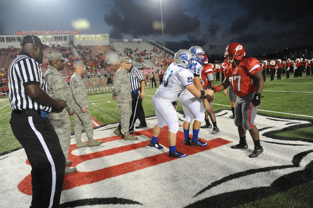 Maj. Gen. Mark Brown, 2nd Air Force commander; Chief Master Sgt. David Staton, 2nd AF command chief, and Brig. Gen. Patrick Higby, 81st Training Wing commander, meet with the football team captains following the coin toss by Staton at the Biloxi High School football game against Ocean Springs High School Oct. 10, 2014, at the Biloxi football stadium.  Staton tossed the coin to determine which team would receive the ball first. Ocean Springs defeated Biloxi 35-21.  (U.S. Air Force photo by Kemberly Groue)