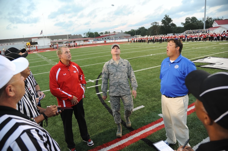 Chief Master Sgt. David Staton, 2nd Air Force command chief, tosses the coin for the official coin toss as the head coaches and referee staff watch closely during the Biloxi High School football game against Ocean Springs High School Oct. 10, 2014, at the Biloxi football stadium. Staton tossed the coin to determine which team would receive the ball first.  Ocean Springs defeated Biloxi 35-21.  (U.S. Air Force photo by Kemberly Groue)