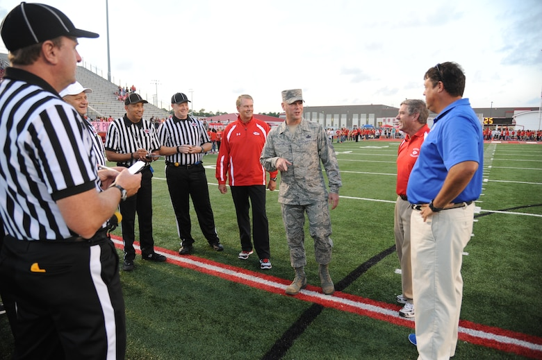 Chief Master Sgt. David Staton, 2nd Air Force command chief, meets with the head coaches and referee staff prior to the official coin toss during the Biloxi High School football game against Ocean Springs High School Oct. 10, 2014, at the Biloxi football stadium. Staton tossed the coin to determine which team would receive the ball first.  Ocean Springs defeated Biloxi 35-21.  (U.S. Air Force photo by Kemberly Groue)