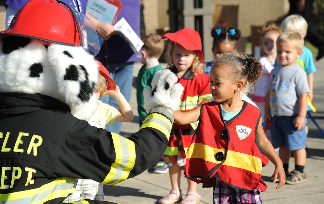 The daughter of Tech. Sgt. Jasmine Howell, 81st Force Support Squadron, gives a high-five to Sparky the Fire Dog Oct. 7, 2014, at the child development center, Keesler Air Force Base, Miss., during a visit from the Keesler Fire Department for fire prevention week. Throughout fire prevention week the Keesler Fire Department conducted random fire drills, toured various facilities with Sparky the Fire Dog, passed out fire safety handouts and fire hats for children and provided stove and fire extinguisher demonstrations.  The week–long event ended with an open house at the fire station 10 a.m. to 2 p.m. Oct. 11.  (U.S. Air Force photo by Kemberly Groue)