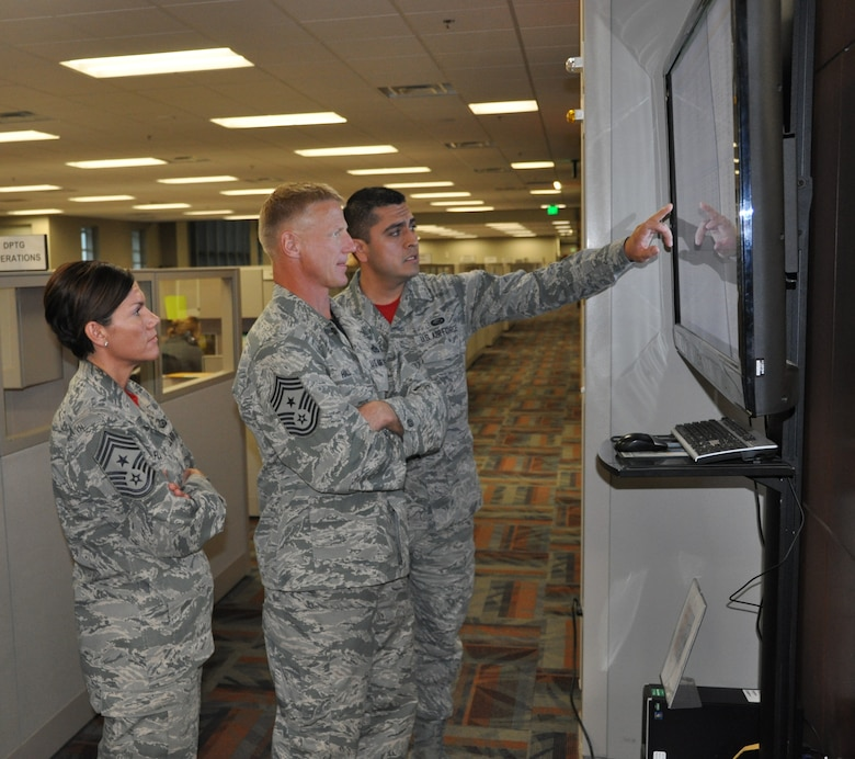 Senior Airman Samuel Uribe-Talamantes, Air Reserve Personnel Center status systems technician, briefs Chief Master Sgt. Craig Hall, 460th Space Wing command chief, on the ARPC call center agents' log time and ready, non-ready status screen as Chief Master Sgt. Ruthe Flores, ARPC command chief, stands by Oct. 10, 2014, on Buckley Air Force Base, Colo. Hall came to ARPC to say farewell to service members and civilians, thanking them for their service and letting them know the impact they left on him. (U.S. Air Force photo/Tech. Sgt. Rob Hazelett)