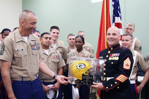 U.S. Marine Corps Gunnery Sgt. John D. Ward, right, receives a retirement gift from U.S. Marine Corps Sgt. Maj. William Sweeney, Recruiting Station Frederick's sergeant major, before the start of his retirement ceremony in Frederick, Maryland, Sept. 25, 2014. Ward, a career recruiter, retired after 20 years of service. The Green Bay Packers helmet was signed by the many Marines who have worked tirelessly by Ward's side during his tour as a recruiter and staff noncommissioned officer in charge. (U.S. Marine Corps photo by Cpl. Amber Williams/Released)