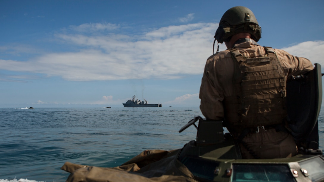 Sgt. William J. Puckett, an assault amphibious crew chief with Alpha Company, 2nd Assault Amphibian Battalion, 2nd Marine Division, watches from the turret of his AAV as Marines with his unit conduct a Gator Square after disembarking from the USS Whidbey Island off the coast of Camp Lejeune, N.C., Sept. 10, 2014. Alpha Company Marines spent two days on Onslow Beach testing their AAV's before taking them out to sea to board the USS Whidbey Island in order to conduct ship operations. (U.S. Marine Corps photo by Lance Cpl. Justin Updegraff / Released)