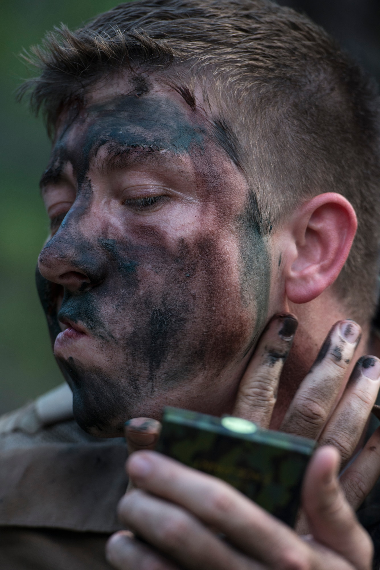 Maj. Rob Gatti applies paint to his face in preparation for a combat survival refresher course Oct. 9, 2014, at Joint Base Pearl Harbor-Hickam, Hawaii. The survival, evasion, resistance and escape combat survival refresher course is designed to familiarize aircrew members with combat skills learned through hands-on training in a realistic environment. Gatti is from the 65th Airlift Squadron. (U.S. Air Force photo/Staff Sgt. Christopher Hubenthal)