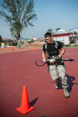 1st Lt. Andrew Davenport, member of team miscellaneous, does the tool serpentine carry during the Firefighter Challenge for Fire Prevention Week at Osan Air Base, Republic of Korea, Oct. 10, 2014. The challenge consisted of five obstacles; the bongo push, tool serpentine carry, hose pull, dummy drag and bucket brigade. (U.S. Air Force photo by Senior Airman Matthew Lancaster)