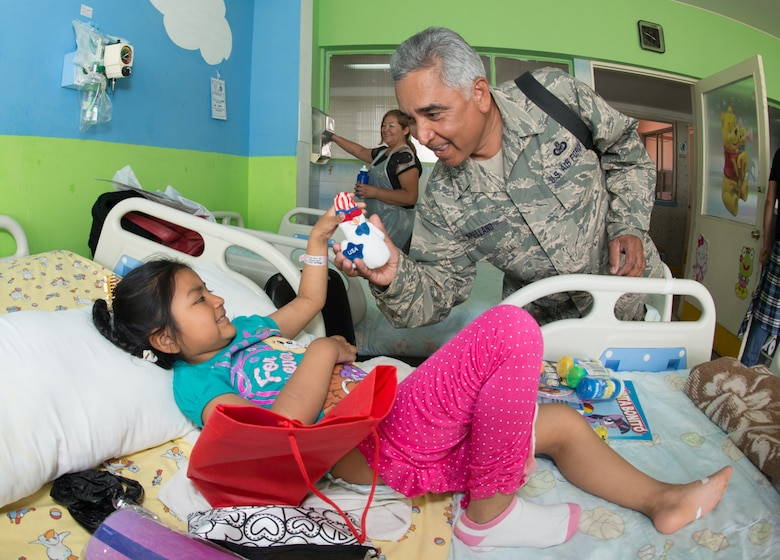 Senior Master Sgt. Mike Arellano from the 149th Fighter Wing, Texas Air National Guard, along with the other countries participating in the Salitre 2014, visit the children's ward at the Leonardo Guzman Regional Hospital, Antofagasta, Chile, to distribute gifts and bring a few moments of joy to the awaiting hospitalized children, Oct. 11. Salitre is a Chilean-led exercise where the U.S., Chile, Brazil, Argentina and Uruguay, focus on increasing interoperability between allied nations. (Air National Guard photo by Senior Master Sgt. Elizabeth Gilbert/released)