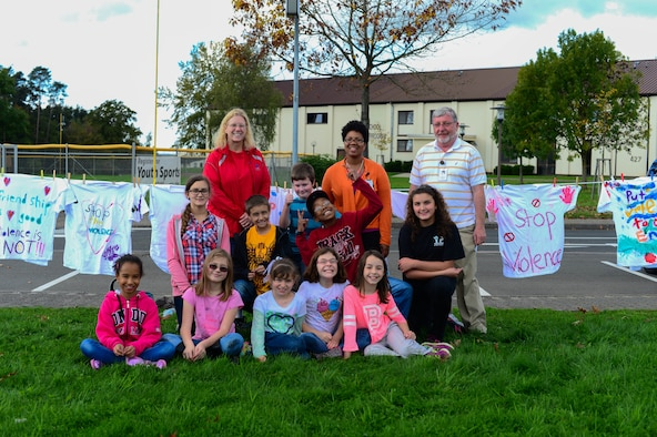 Karen Pilalas, 4th-grade child and youth programs assistant at the 52nd Force Support Squadron School Age Program, poses with her class in front of the School Age building on Spangdahlem Air Base, Germany, Oct. 14, 2014. The clothes line displaying painted shirts brings awareness to domestic violence and is hung behind the class. 52nd Medical Operations Squadron Family Advocacy hosted the shirt hanging at the School Age Program facility to help encourage children to recognize domestic violence and report it to the authorities. (U.S. Air Force photo by Airman 1st Class Kyle Gese/Released)
