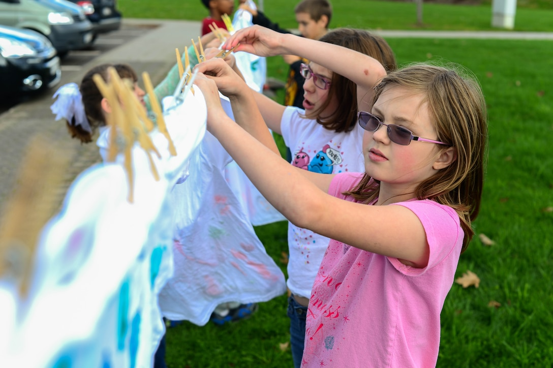 Shelby Carter, daughter of Wendy Joramo-Carter and Shane Carter, helps hang shirts on a clothes line at the school age building on Spangdahlem Air Base, Germany, Oct. 15, 2014. Children hung painted shirts to raise awareness for domestic violence. The 52nd Medical Operations Squadron Family Advocacy partnered with the 52nd Force Support Squadron School Age Program and Teen Center to educate children about preventing the violence. (U.S. Air Force photo by Airman 1st Class Kyle Gese/Released)