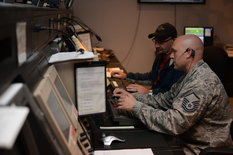 Master Sgt. Andrew Jackson, Combat Readiness Training Center RADAR approach control chief controller, and Jeff McCluskey, Federal Aviation Administration air traffic control specialist, work together to control airspace at the ATC center at Volk Field Air National Guard Base, in Camp Douglas, Wisconsin, Oct. 6, 2014. The FAA sent civilian ATC specialists to Volk Field following a fire at the Chicago ATC Center. Two of the FAA ATC specialists were also Volk Field guardsmen. (Air National Guard photo by Senior Airman Andrea F. Rhode)