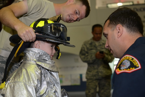 Members of the 36th Civil Engineer Squadron Fire and Emergency Services assist a student from Andersen Elementary School gear up on Andersen Air Force Base, Guam Oct. 8, 2014. 36th CES visited the elementary school part of Fire Prevention week to raise awareness. (U.S. Air Force photo by Airman 1st Class Adarius Petty/Released)