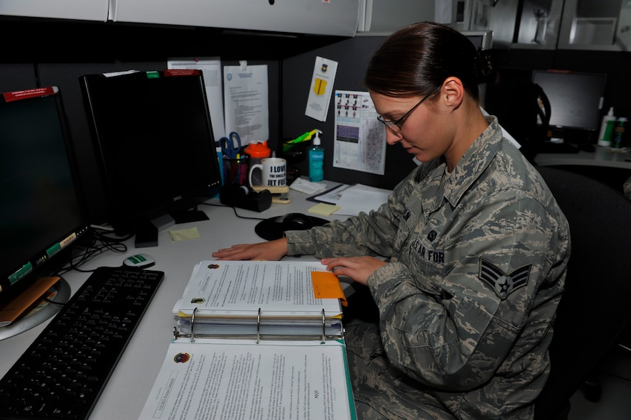Senior Airman Amber Devlin, 694th Intelligence, Surveillance and Reconnaissance Group program manager, updates the training continuity binder Oct. 15, 2014, on Osan Air Base, Republic of Korea. Devlin was selected to be a part of the 15-player roster on the Air Force's Women's softball team. (U.S. Air Force photo by Senior Airman David Owsianka)