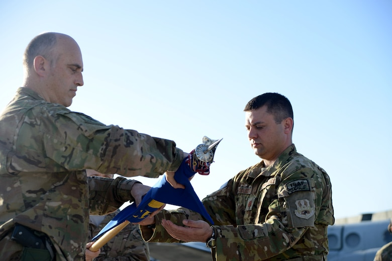 U.S. Air Force Col. Jon Wilkinson, 455th Expeditionary Operations Group commander works with Maj. Tanner Woolsey, 4th Expeditionary Reconnaissance Squadron commander, to roll the squadron's guidon before sheathing it during the 4 ERS transition of authority ceremony at Bagram Airfield, Afghanistan Oct. 1, 2014. With the inactivation of 4 ERS, Joint Task Force Thor is now the lead for the MC-12W mission in Afghanistan. (U.S. Air Force photo by Master Sgt. Cohen A. Young/Released)