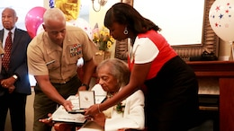 Ella Jackson, a 93-year-old widow, receives a Congressional Gold Medal replica in lieu of her late husband, Master Sgt. George Jackson, in Port Royal, S.C., Oct. 2. George Jackson enlisted in the Marine Corps in 1942 and retired after 27 years of service in 1969. Brigadier General Terry Williams, the first African-American commanding general of Marine Corps Recruit Depot Parris Island, presented Jackson with the medal at a ceremony. In 2012, congress awarded the Montford Point Marines with the Congressional Gold Medal, the United States' highest civilian award bestowed by congress.