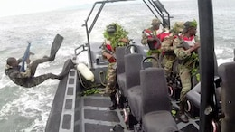 A service member with the Cameroonian Naval Commando Company jumps into the water to establish beach security for follow-on operations. The COPALCO worked with Marines, Sailors and Coast Guardsmen part of Special Purpose Marine Air Ground Task Force-Crisis Response-Africa, on marksmanship, boat operations, patrolling and noncommissioned officer leadership.