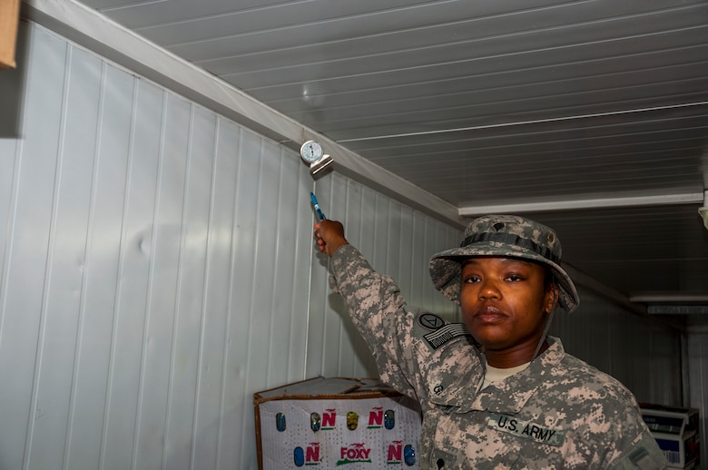 Army Spc. Juanetta Goldwire, 719th Medical Detachment Veterinary Services points at a temperature gage that she checks to determine if food is being stored at the correct temperatures in a refrigerated container outside the main dining facility at The Rock Aug. 7, 2014. As a food inspector, Goldwire's primary mission is to reduce the risks to public health associated with diseases and other health hazards in food that is designated for more than 3,000 Airmen, Soldiers, Marines, Sailors and contractors reasons. Goldwire deployed here from the 719th MDVS, Fort Sheridan, Illinois. (U.S. Air Force photo by Senior Master Sgt. Allison Day)