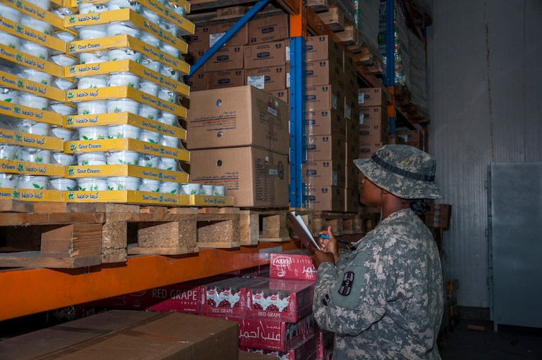 Army Spc. Juanetta Goldwire, 719th Medical Detachment Veterinary Services checks the expiration label on food stored at the rations warehouse at The Rock Aug. 7, 2014. As a food inspector, Goldwire's primary mission is to reduce the risks to public health associated with diseases and other health hazards in food that is designated for more than 3,000 Airmen, Soldiers, Marines, Sailors and contractors reasons. Goldwire deployed here from the 719th MDVS, Fort Sheridan, Illinois. (U.S. Air Force photo by Senior Master Sgt. Allison Day)
