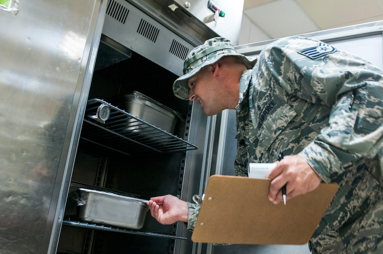Air Force Staff Sgt. James Rodenberg, 386th Expeditionary Medical Group public health technician inspects food in a refrigerator during his inspection of the main dining facility at The Rock Sept. 23, 2014. Rodenberg conducts inspections two times each month at both dining facilities to promote good personal hygiene across the base and to ensure that facilities are operating in accordance with governing regulations. He deployed from 96th Aerospace Medicine Squadron Eglin Air Force Base, Fla., in support of Operation Enduring Freedom and is a native of Crestview, Fla. (U.S. Air Force photo by Senior Master Sgt. Allison Day)