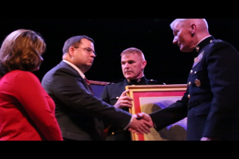 """Lt. Gen. John Toolan, Marine Corps Forces, Pacific commander, presents a certificate to Rick and Monique Sprinkle during an honorary Marine ceremony in Jonesville, Virginia on Oct. 15, 2014. Rick and Monique's son, Jacob, received the title """"honorary Marine"""" posthumously during the ceremony."""