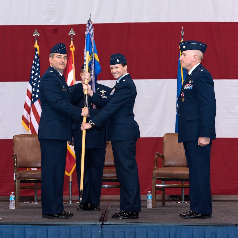 Lt. Col. Carol O'Neil, center, is all smiles as she accepts the guidon from Col. Alain Poisson, 552nd Operations Group commander, shortly after assuming command of the 965th Airborne Air Control Squadron during a ceremony Oct. 2 in Bldg. 230, Dock 2. Colonel O'Neil replaces Lt. Col. Anthony Kleiger, right, who will be headed to United States Pacific Command at Camp Smith, Hawaii, to work in operations there. Colonel O'Neil had previously served as the 552nd Air Control Wing director of staff. Colonel Poisson presided over the ceremony attended by a host of family, friends and co-workers. (Air Force photo by Staff Sgt. Kristopher Gooden)