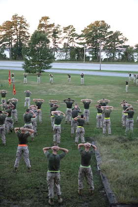 The Ground Combat Element Integrated Task Force Marine noncommissioned officers lead cool-down stretches and exercises after the task force conducted a three-mile run aboard Marine Corps Base Camp Lejeune, North Carolina, Oct. 17, 2014. The task force conducted the run to build unit cohesion and maintain physical fitness across the unit. From October 2014 to July 2015, the GCEITF will conduct individual and collective level skills training in designated ground combat arms occupational specialties in order to facilitate the standards based assessment of the physical performance of Marines in a simulated operating environment performing specific ground combat arms tasks. (U.S. Marine Corps photo by Sgt. Alicia R. Leaders/Released)